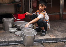 Boy doing the dishes on the sidewalk. Stock Image