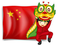 A boy doing dragon dance in front of flag of China Stock Image