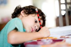 Boy doing his homework. Young boy doing his homework at home royalty free stock images