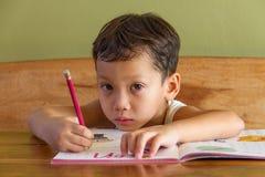 Boy doing his homework. A boy doing his homework Stock Photo