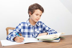 A boy is doing his homework. A handsome teenage boy is doing his homework stock images
