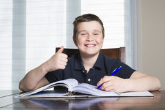 Boy doing his homework at home. A boy doing his homework at home Stock Photo