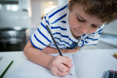 Boy doing his homework. At home in the kitchen Stock Images