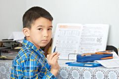 Boy is doing his homework. At the table Stock Photos