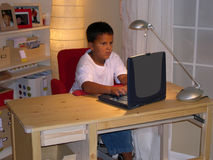 Boy Doing Homework. Homework is fun when you have a notebook laptop to use stock image