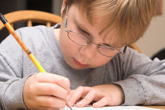 Boy Doing Homework. A young boy studying, doing his homework Stock Images