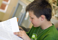 Boy doing homework. A boy sitting at a table in the living room, doing his homework. He is checking his spelling at the back of the notebook Royalty Free Stock Image
