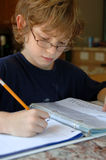 Boy doing homework. A 9 year old boy wearing glasses and doing his homework Royalty Free Stock Image