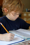 Boy doing homework. A 9 year old boy wearing glasses and doing his homework Royalty Free Stock Photos