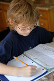 Boy doing homework. A 9 year old boy wearing glasses and doing his homework Stock Photography