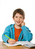 Boy doing homework. Happy young boy smiling whilst doing homework Royalty Free Stock Photography