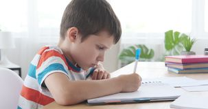 Boy doing homework in book. Boy writing in notebook while sitting at desk and doing homework stock footage