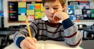 Boy doing homework in classroom 4k stock video footage