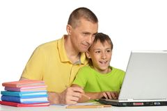Boy doing homework with father Stock Photography