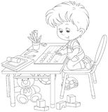 Boy doing homework after his game with toys. Little schoolboy writing in an exercise book with samples of letters, a black and white vector illustration in a Royalty Free Stock Images