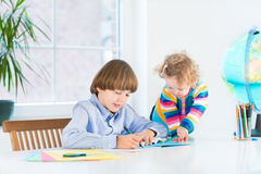 Boy doing homework and his sister watching him. Young school boy doing his homework and his toddler sister watching him in a white room next to a window royalty free stock photo