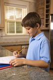 Boy doing homework at kitchen counter. Stock Image