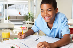 Boy Doing Homework In Kitchen. Smiling To Camera Stock Photos