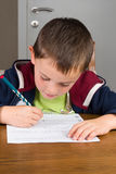 Boy doing homework. In a living room Royalty Free Stock Image