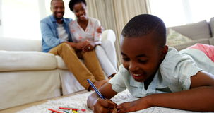 Boy doing homework in living room and parents sitting on sofa stock video footage