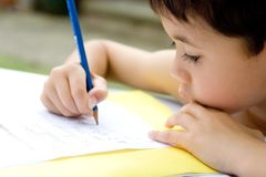 Boy doing homework, outdoors Stock Images