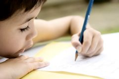 Boy doing homework, outdoors. stock image