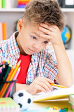Boy doing homework. Portrait of despairing adolescent boy in school classroom Stock Image