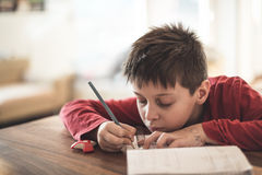 Boy doing homework reluctantly Royalty Free Stock Images