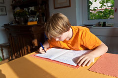 Boy doing homework for school at Royalty Free Stock Images