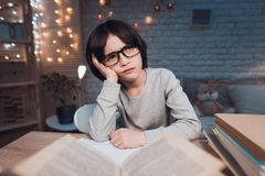 Boy is doing homework for school surrounded by books at night at home. royalty free stock photo
