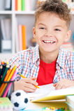 Boy doing homework. Smiling adolescent boy doing homework at the table Stock Images