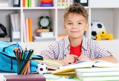 Boy doing homework. Smiling adolescent boy doing homework at the table Stock Photos