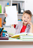 Boy doing homework. Smiling adolescent boy doing homework at the table Stock Photo