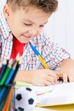 Boy doing homework. Smiling adolescent boy doing homework at the table Royalty Free Stock Images