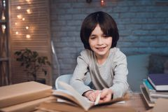 Boy is doing homework surrounded by books at night at home. stock images