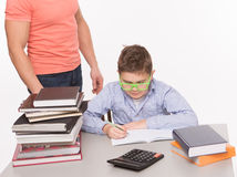 Boy doing homework at the table. Boy doing his homework while his father standing near the table and looking at him. There are many books on the table Royalty Free Stock Photography