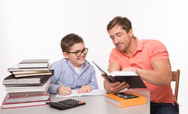 Boy doing homework together with his father. Father teaching his son. Father explaining difficult math theories to his son. Son smiling and looking into the book Royalty Free Stock Photos