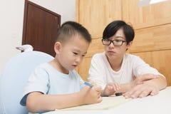 Boy doing homework with tutorship Royalty Free Stock Image