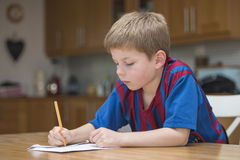 Boy doing homework. Boy writing and doing homework in the kitchen Royalty Free Stock Photos