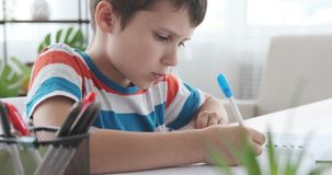Boy holding pen writing in book. Boy doing homework writing with pen in notebook stock footage
