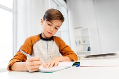 Boy doing homework and writing to notebook at home stock photos