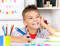Boy doing homework. Young boy sitting at desk in the classroom, doing homework at the table Stock Images