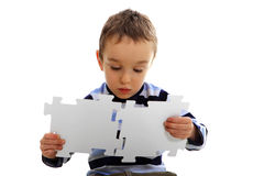 Boy doing a jigsaw on the white background royalty free stock photo