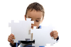 Boy doing a jigsaw on the white background stock photos
