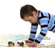 Boy doing a jigsaw on the white background stock image