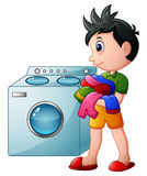 Boy doing laundry with washing machine Stock Photography