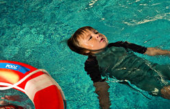 Boy doing Lifesaving Floating on Water. Boy floating still on his back on water, practicing waiting for Life Ring Buoy. Lifesaving practice Royalty Free Stock Image