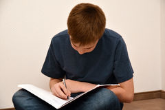 Boy doing maths homework. Concentrated teenager boy sitting on the floor, doing his maths school homework royalty free stock photo