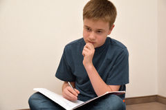 Boy doing maths homework. Concentrated teenager boy sitting on the floor, doing his maths school homework stock image