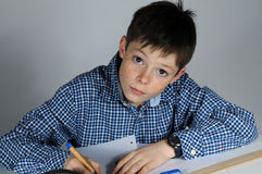 Boy doing maths homework. Concentrated teenager boy sitting at his desk  doing his maths school  homework Royalty Free Stock Photos